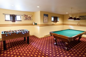 Game room with pool table, foosball, exercise bike, and workout equipment