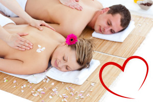 Beautiful young couple receiving a back massage against heart